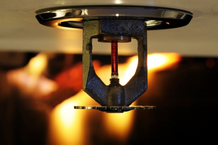 Close up image of fire sprinkler with fire in background