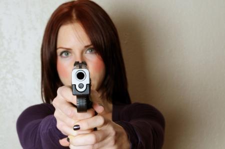 mujer con pistola: Imagen de mujer apuntando una pistola a alguien rompiendo e introduciendo  Foto de archivo