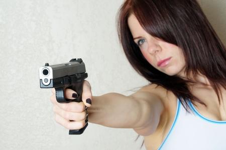 mujer con pistola: Foto de ca��n de poing mujeres j�venes a alguien rompiendo e introduciendo  Foto de archivo