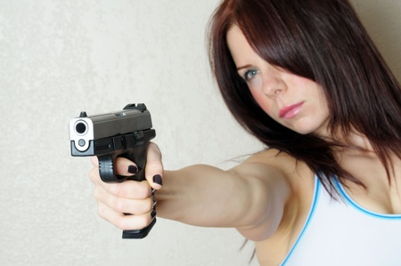 Image of young female poing gun at someone breaking and entering