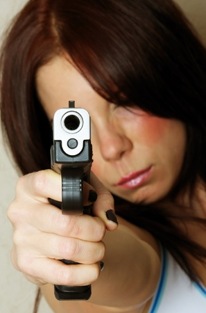 Close-up image of young attractive female pointing gun.  Focus is on barrel of gun. Stock Photo - 8281163