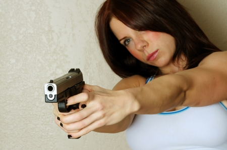 armed services: Close up image of young attractive female pointing gun at someone breaking and entering Stock Photo
