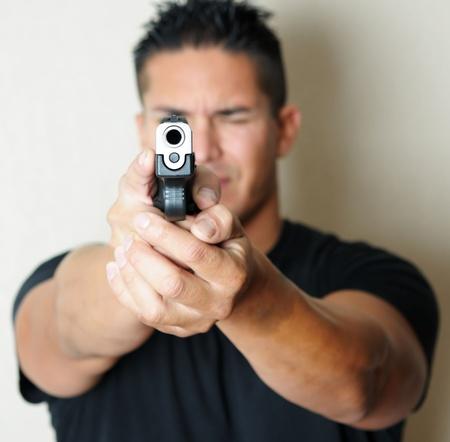 guns: Image of young male pointing gun.  Focus on barrel of gun. Stock Photo