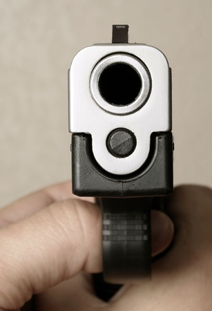 Close up isolated image of person pointing pistol