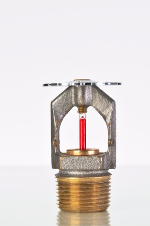 Close up image of fire sprinkler with fire in background. Fire sprinklers are part of an integrated water piping system designed for life and fire safety.