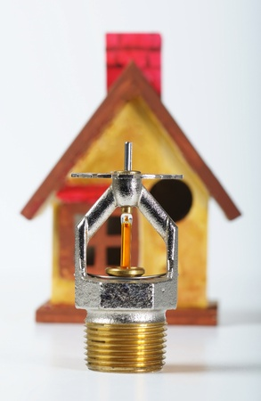 Close up image of fire sprinkler on white. Fire sprinklers are part of an integrated water piping system designed for life and fire safety.  Replica of house in background