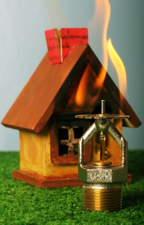 Close up image of fire sprinkler. Fire sprinklers are part of an integrated water piping system designed for life and fire safety. Replica of house on fire added to background.  Stock Photo