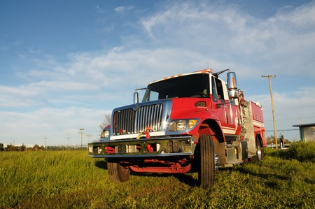 Image of fire truck in field with blue sky background