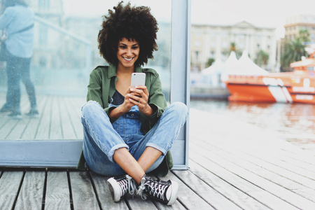 a dark-skinned beautiful girl with afro hair talking through a webcam with her friends.