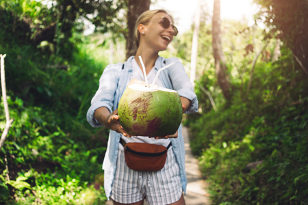 Blonde tourist girl is offering a coconut cocktail on a green jungle background. Stock Photo