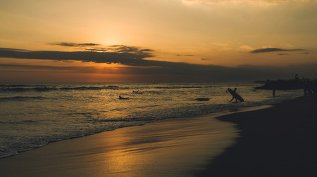 Colorful seascape at the nightfall with silhouettes of surfers. Charming sunset at the tropical sand beach. Friends are spending summer vacation swimming at the tropical sea with no waves.