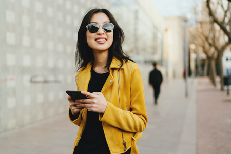 Half length portrait of a beautiful smiling asian woman in a sunglasses with long dark hair wearing yellow leather jacket chatting online by a mobile phone while standing on blurred street background.