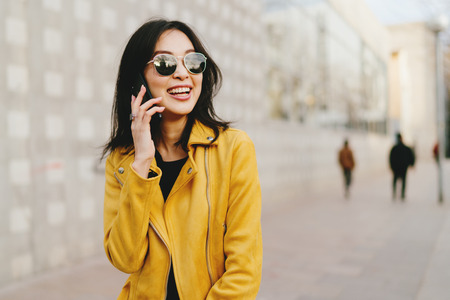 Sonriente mujer asiática con cabello largo y oscuro en gafas de sol hablando por un teléfono inteligente mientras camina por la calle de la ciudad. Joven emprendedor haciendo llamadas de negocios a través de un teléfono móvil mientras va al espacio de coworking. Foto de archivo