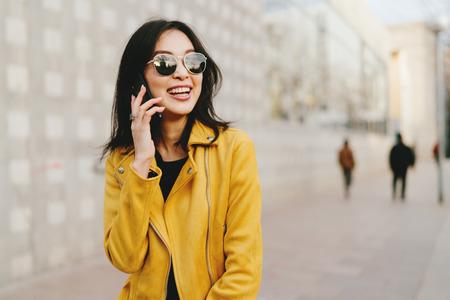Uśmiechnięta azjatycka kobieta z długimi ciemnymi włosami w okularach przeciwsłonecznych, rozmawia przez smartfona podczas spaceru ulicą miasta. Młody przedsiębiorca wykonujący rozmowy służbowe przez telefon komórkowy w drodze do coworkingu. Zdjęcie Seryjne