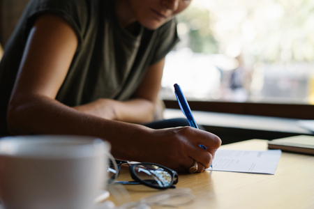 Cropped photo of a females hand writing something on the papers. Student girl is studying at the coffee break time in a cafe. Female is making notes while sitting at the table at coffee shop. Stock Photo