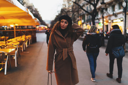 International student girl in stylish clothes walking the street on a weekend days. Tourist female exploring the city during weekend journey. Hipster girl in stylish coat and beret lounging outdoors Stockfoto - 105969421