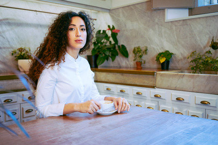 young attractive girl drinking coffee in a coffe-shop.Beautiful business woman drinking coffee before a meeting with a business-partner