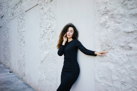young beautiful female student with long curly hair wearing a tight black dress posing against a white brick wall with copy space area for your text o design and talking on the digital smart-phone