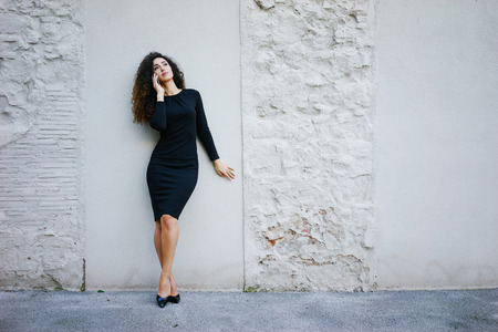 young beautiful business woman with long curly hair wearing a tight black dress posing against a white brick wall with copy space area for your text o design and talking on the digital smart-phone