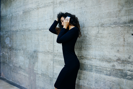 young beautiful business woman with long curly hair while posing against gray concrete wall with copy space for your text o design and talking on smart-phone