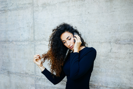 Portreit of a young beautiful student with long curly hair while standing against gray concrete wall with copy space for your text o design