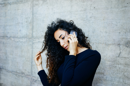 Portreit of a young beautiful business woman with long curly hair while standing against gray concrete wall with copy space for your text o design