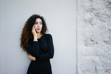 young beautiful business woman with long curly hair wearing a black dress standing on a white brick wall background with copy space area for your text o design,talking on smart-phone Imagens