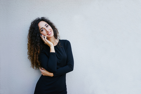 young beautiful business woman with long curly hair wearing a black dress posing on a white background with copy space area for your text o design,talking on smart-phone and smiling at the camera