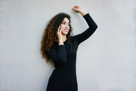 young smiling beautiful business woman with long curly hair wearing a tight black dress posing on a white wall background with copy space area for your text o design and talking on the smart-phone