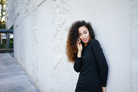 young beautiful girl with long curly hair wearing a tight black dress posing against a white brick wall with copy space area for your text o design and talking on the digital smart-phone Imagens