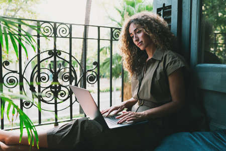 Professional blogger searching the information online on a laptop computer while working in a comfort from home. Beautiful woman sitting on a floor beside an open balcony with a netbook on her knees.
