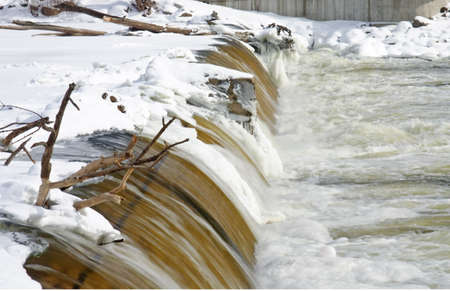 ice dam: Water flowing over a dam with log snags in winter ice and snow