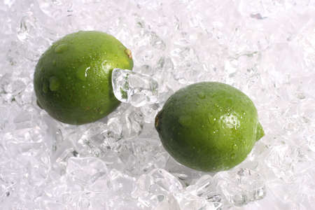 Two whole limes on a bed of ice 스톡 콘텐츠
