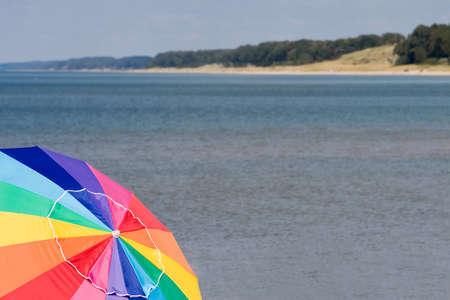 バック グラウンドでのミシガン湖の海岸線とカラフルなビーチ傘 写真素材