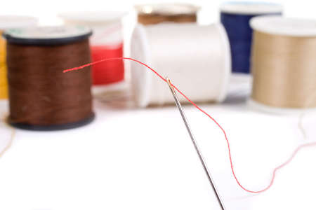 darn: Sewing needle threaded with red, various colored spools in background