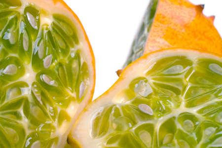 A juicy sliced open horned or Kiwano melon showing the seeds and yellow-green flesh Stock Photo