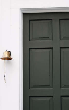 hinged: A brass bell hangs next to the green door of a historic building