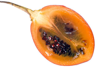 tamarillo: Cut half of a fresh Tamarillo fruit showing its deep red seeds and tangy sweet flesh Stock Photo