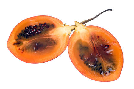 tangy: Cut halves of a fresh Tamarillo fruit showing its deep red seeds and tangy sweet flesh