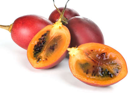 tangy: Whole and halved fresh Tamarillo fruit showing its deep red seeds and tangy sweet flesh