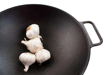 Four garlic bulbs in a black cast iron wok photo