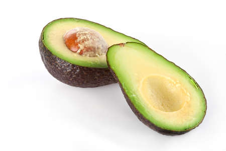 Two hass avocado halves one with pit