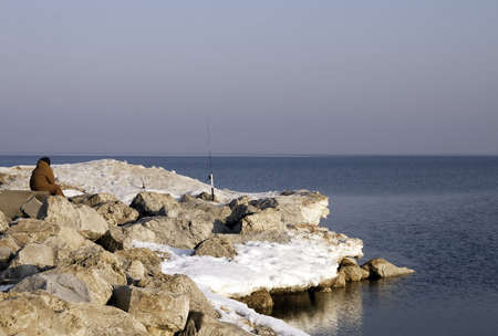 Early spring fishing from the still snow covered rocks at Ottawa beach on Lake Michigan Stock Photo - 6578821