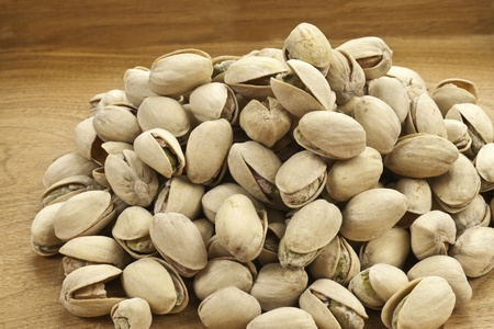 Roasted Pistachio nuts on a wood background