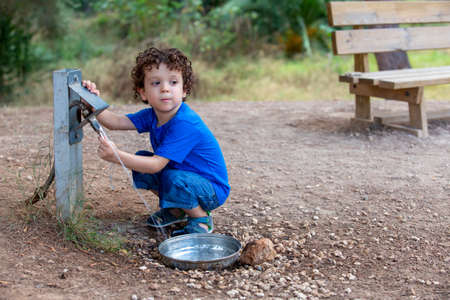 child opening a fountain for animals in park located in the middle of nature,