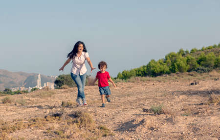 Woman with her son playing chasing him in the field far from the city Stock Photo
