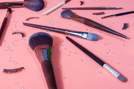 brushes for makeup of different sizes on a pastel background, accompanied by false eyelashes and small diamonds distributed by the set, top and close view,
