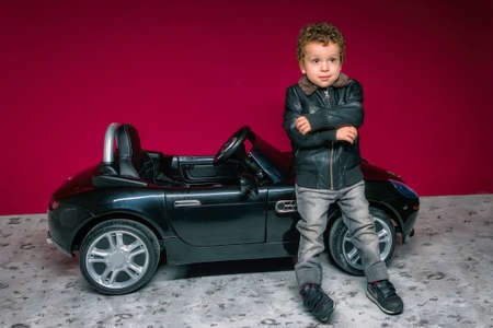 Boy with modern look leaning on electric convertible car suitable for his age Reklamní fotografie
