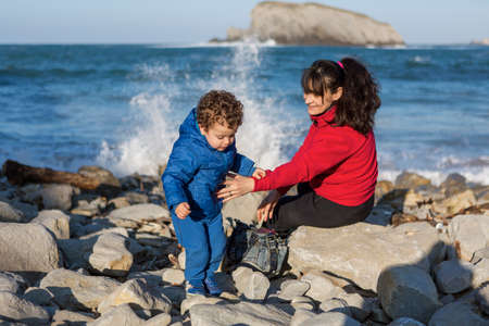 Mother and son spending the afternoon on the rocks by the sea