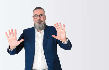 stylishly dressed bearded hipster in blue jacket on white background and copy space, raising hands and showing palms,